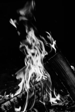 Burning wood logs, cooking on fire, warm evening, sparkles in the air, warm air from the fire. Monochrome Stock Photo