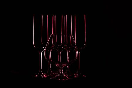 The outlines of transparent glass goblets on a black background. Toned.