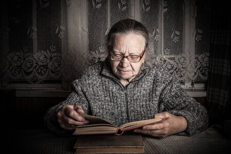 Elderly woman reads book in rustic interior. Toned. Stockfoto