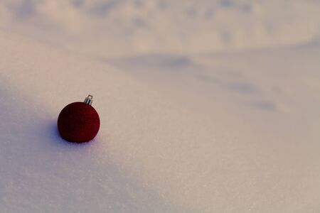 Bright balls on a clean pure snow for natural winter background. New year composition. Shallow depth of field. Selection focus. Toned.