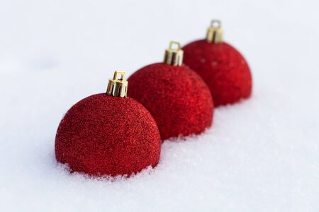 Bright balls on a clean pure snow for natural winter background. New year composition. Shallow depth of field. Selection focus.