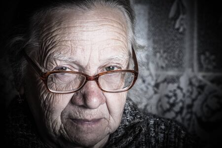 Elderly woman with glasses in rustic interior. Toned. Stockfoto