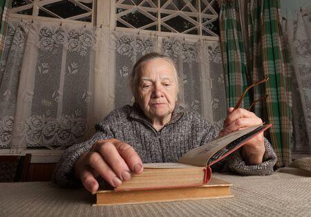 Elderly woman reads book in rustic interior.