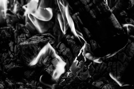 Burning wood logs, cooking on fire, warm evening, sparkles in the air, warm air from the fire. Monochrome 스톡 콘텐츠 - 129245271