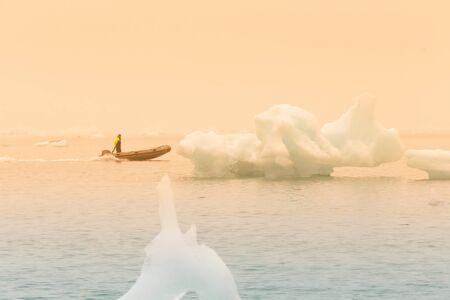 Man on a boat between bizarre ice floes of Iceberg lagoon jokulsarlon on the south of Iceland. Toned. Stockfoto