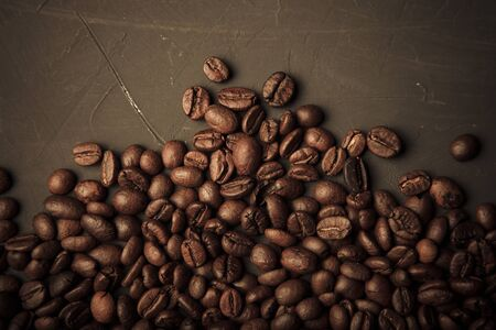 Composition with a coffee beans on a textured plastered background with a variety of arbitrary stains. Toned.