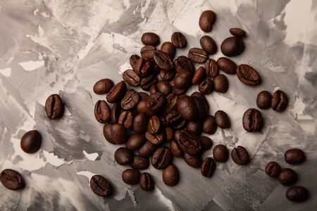 Composition with a coffee beans on a textured plastered background with a variety of arbitrary stains.