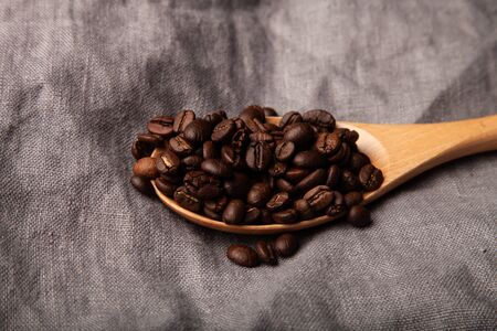 Composition with a coffee beans on a linen napkin for background.