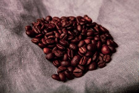 Composition with a coffee beans on a linen napkin for background. Toned.