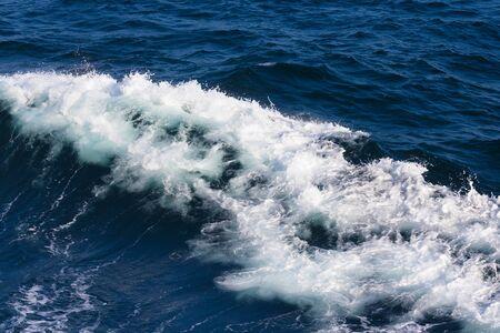 Cresta bianca di un'onda del mare. Messa a fuoco selettiva. Profondità di campo.