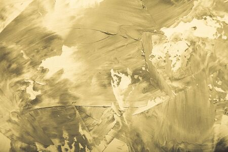 Textured plastered background with a variety of arbitrary stains. Gold. Toned