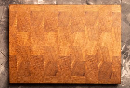 Composition with a cutting board on a textured plastered surface.