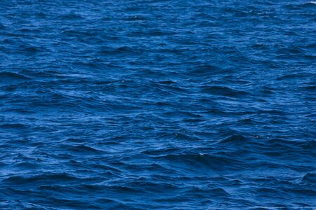 Surface of a calm blue sea. Selective focus. Shallow depth of field.