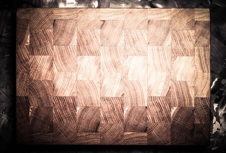 Composition with a cutting board on a textured plastered surface. Toned.