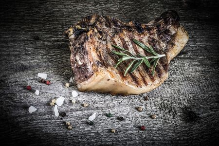 Large piece of fresh pork meat on a bone prepared on a grill pan on old wooden table for background. Toned.
