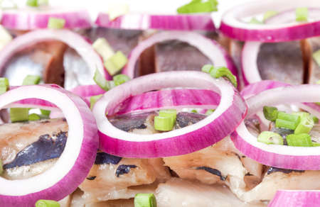 Salted herring with rings of red onion rings on oval plate on a light background. Marinated sliced fish. Traditional russian appetizer.