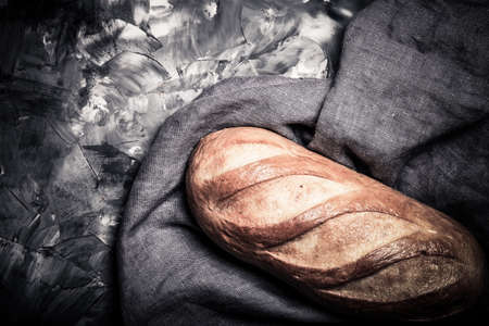 Composition with a bread on a textured plastered surface. Toned. Standard-Bild