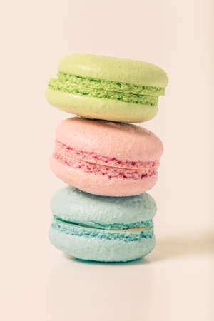 Colorful cake macaroons on a light background. Toned.