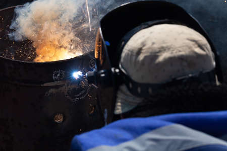 An experienced welder at work. Preparation and welding process of cast iron furnace. Selection focus. Shallow depth of field.