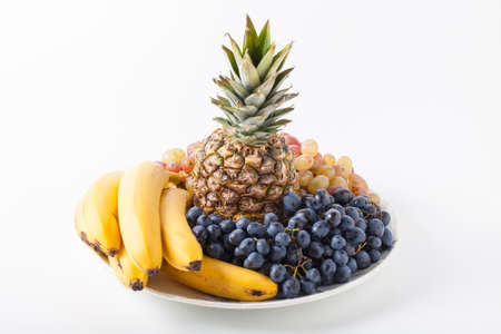 Fruit bouquet with pineapple, banana and grapes on a light background. Standard-Bild
