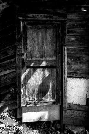 Rickety old barn with wooden door broken. Toned. Standard-Bild