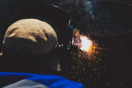 An experienced welder at work. Preparation and welding process of cast iron furnace. Selection focus. Shallow depth of field. Toned.