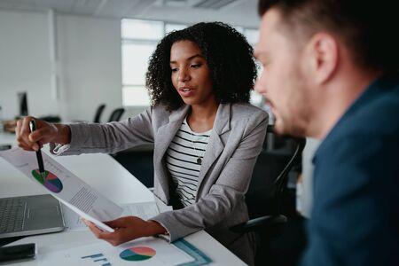 Selbstbewusste junge Geschäftsfrau, die ein Dokument hält, das eine zunehmende Statistik für den Partner im Büro zeigt