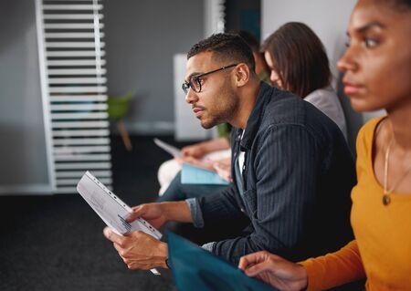 Seitenansicht eines selbstbewussten jungen Afroamerikaners mit Brille, der den Lebenslauf in der Hand hält und auf ein Vorstellungsgespräch mit anderen Kandidaten wartet