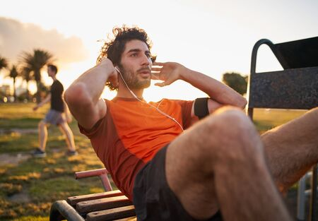 Confident young man listening to music in headphones from smart phone armband doing exercises on public equipment in the outdoor gym at the park
