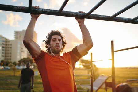 Portrait of a young crossfit sportsman exercising on bar, doing pull-ups for arms and back muscles at the outdoor gym park