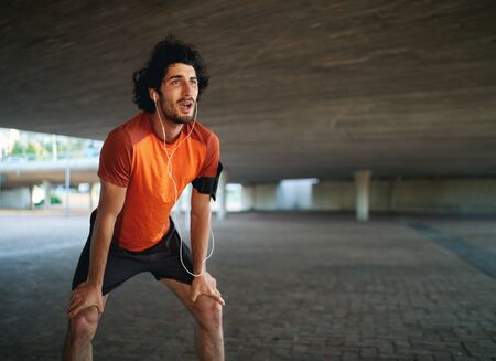 Portrait of a tired caucasian athlete man listening to music taking breathe after a long run under the bridge