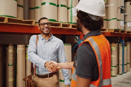 Happy banker in formal clothing shaking hands with warehouse manager after granting him his loan