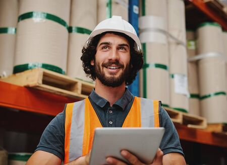 Successful warehouse supervisor smiling and working while holding digital tablet to check inventory and stock wearing white helmet and safety jacket