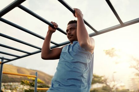 Muscular young athletic fit african american man working out at an outdoor gym doing pull ups Imagens