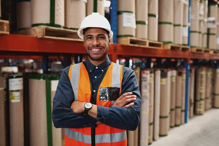 Confident african american man standing with folded arms in manufacturing unit with white helmet and uniform in factory Banque d'images