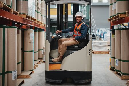 Smiling forklift driver wearing white helmet and vest sitting in machine transporting goods
