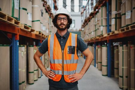 Confident warehouse manager standing in between shelf with hands on waist wearing uniform and hardhat inspecting goods delivery process