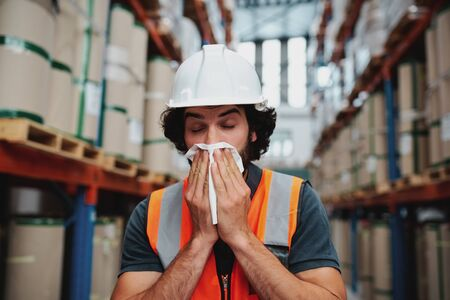 Young warehouse manager coughing and sneezing while feeling sick and covering mouth with handkerchief standing in factory 写真素材