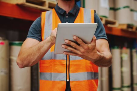 Gros plan d'un employé d'entrepôt en gilet orange tenant une tablette numérique travaillant tout en vérifiant l'inventaire et la commande