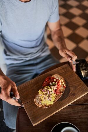 Closeup of young man eating italian bruschetta with coffee in cafe holding fork and knife Banco de Imagens