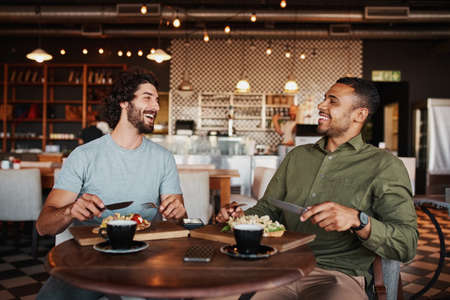 Friends enjoying italian brischetta food in cafe with coffee while laughing during conversation