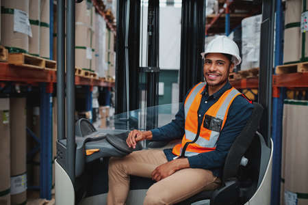 Happy young african forklift manager transporting goods from one shelf to another while looking in camera in warehouse