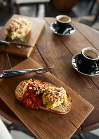 Closeup of single piece of italian bruschetta with cheese pasta toppings and red tomato sauce served with coffee in cafe