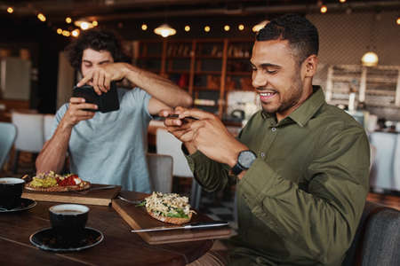 Young afro-americna man with caucasian friend clicking photo of italian bruschetta with coffee in cafe while enjoying lunch Banco de Imagens