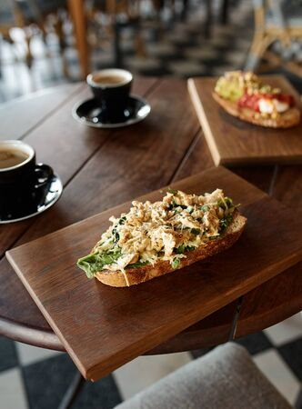 Closeup of single piece of italian bruschetta with cheese pasta toppings served with coffee in cafe Banco de Imagens