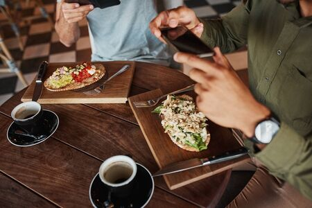Closeup of man hand clicking photo of italian bruschetta with coffee in cafe while enjoying lunch