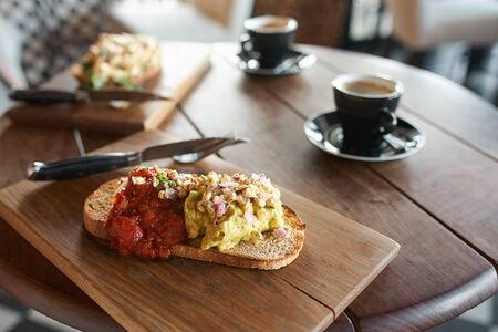 Single piece of italian baguette with cheese pasta toppings and red tomato sauce served with coffee in cafe