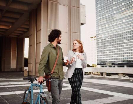 Geschäftsmann mit Fahrrad und Umhängetasche, die mit einer Frau spazieren geht, die Einwegkaffeetasse hält