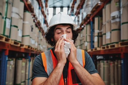 Young sick african warehouse worker blowing nose while working wearing safety vest 写真素材