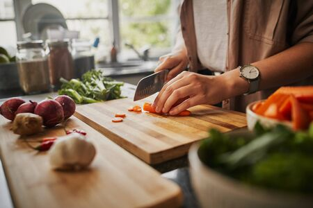 Closeup of young female hands chopping fresh orange carrot on board while in modern kitchen - healthy food to boost the immune system Stok Fotoğraf